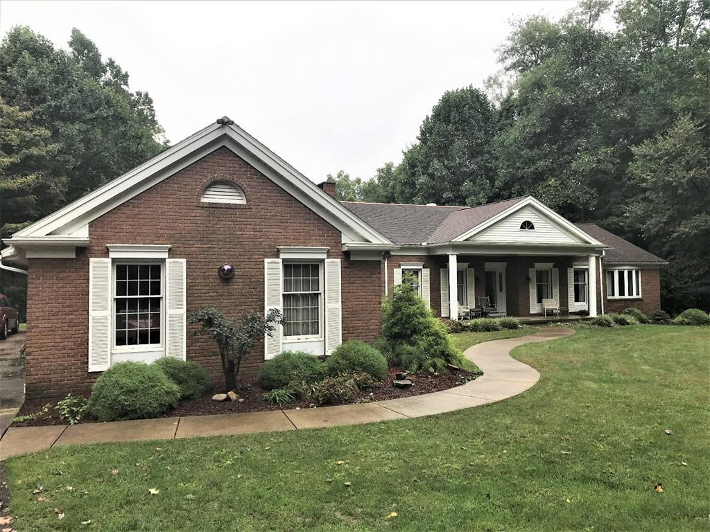 Custom-Built Brick Home with two fireplaces and 3+ car attached garage in a private wooded setting.