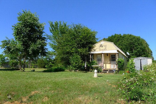 Only about 90 minutes from Dallas and 15 mins from Palestine, but worlds away with its serenity is this 1 Room Tiny house style cabin on 9.75 acres.  If you've been looking for your happy place, this is it! Cabin is located on a clearing at the front of the property and the rest of the property is mostly treed including pines, dogwoods and plenty of wildlife!  Land has nice elevation changes and a beautiful section of Holly Springs Branch Creek running through it. Electric, water and septic system on property. Cabin is livable, but needs some finishing touches. Great place for a weekend retreat, full time living or to build your dream house! Also has a concrete pad and underground storage containers. Shown by advance appointment only -