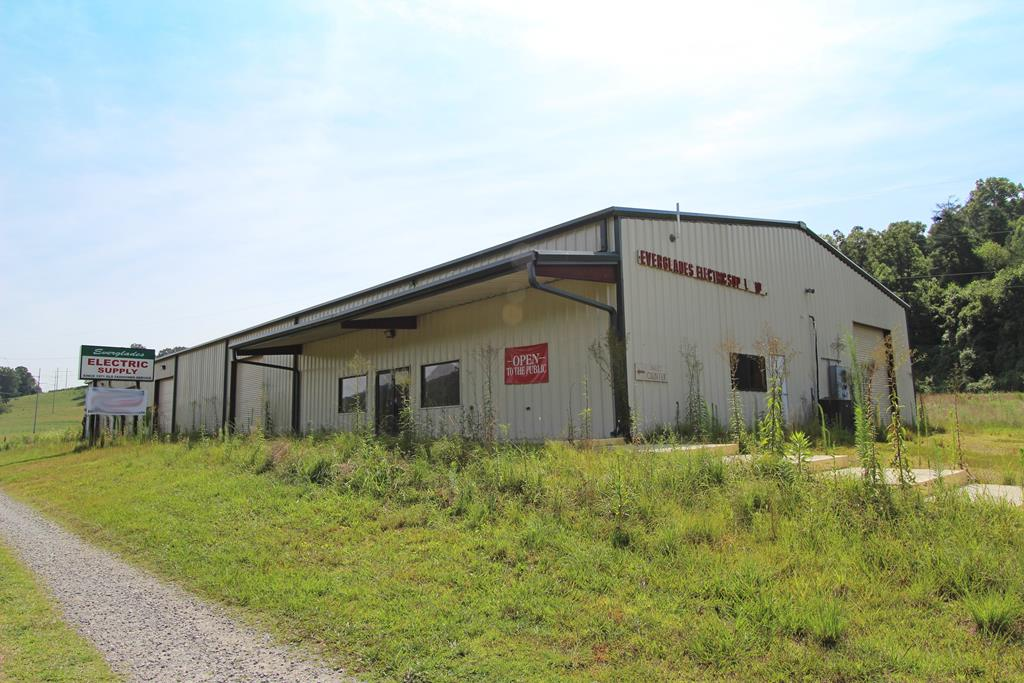 GREAT Commercial Building with 74 Frontage! Great visibility! 10,500+/- square feet of space that can be utilized for many different opportunities. This building has a retail store front, office area, and a huge open warehouse area. Complete with 9 LARGE bay doors and many access doors, this building is very flexible - utilize it all for yourself or easily divide and lease out sections. With 4.16+/- acres, LAND is FLAT and amazing! Lots of area gives you room for parking, storage, and much more!