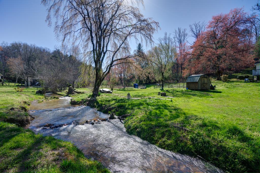 Picturesque mountain setting with a large branch running the entire width of the property.  Sit on your front porch and watch the water roll by.  2.33 acres of gentle laying land, perfect for gardening, goats, chickens, rabbits and more!! Established apple trees in back, with plums, blueberries, and muscadine grape vines out front. 8x8 wood storage bldg, 10x16 metal storage bldg with work space. 3 bedroom, 2 bath Palm Harbor modular, make a great year round residence or second home.  New flooring throughout.  Call to schedule your showing today!