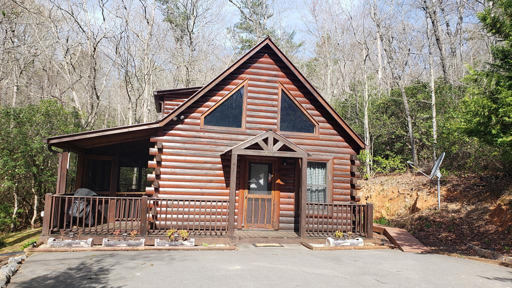 Log cabin in the woods. Fully furnished log cabin on a spring fed creek emptying into Madison Pond. Cabin has all wood interior, 2 large screened porch areas with a hot tub. Seller has made pathways through the Laurels to a fire pit, picnic table, and a nice flowing creek. You can hear the creek from the hot tub and porches. Bedroom on main floor has a queen pull-out sofa and a Jack n Jill bath. Loft bedroom has a queen size bed and adjoining bath with office nook and desk. Stacked washer and dryer on the main level. Road and driveway to the cabin is paved. Small community of 14 Log cabins. Shared well. 11' X 16' workshop with electric. Easy drive to downtown Murphy and Blue Ridge GA.