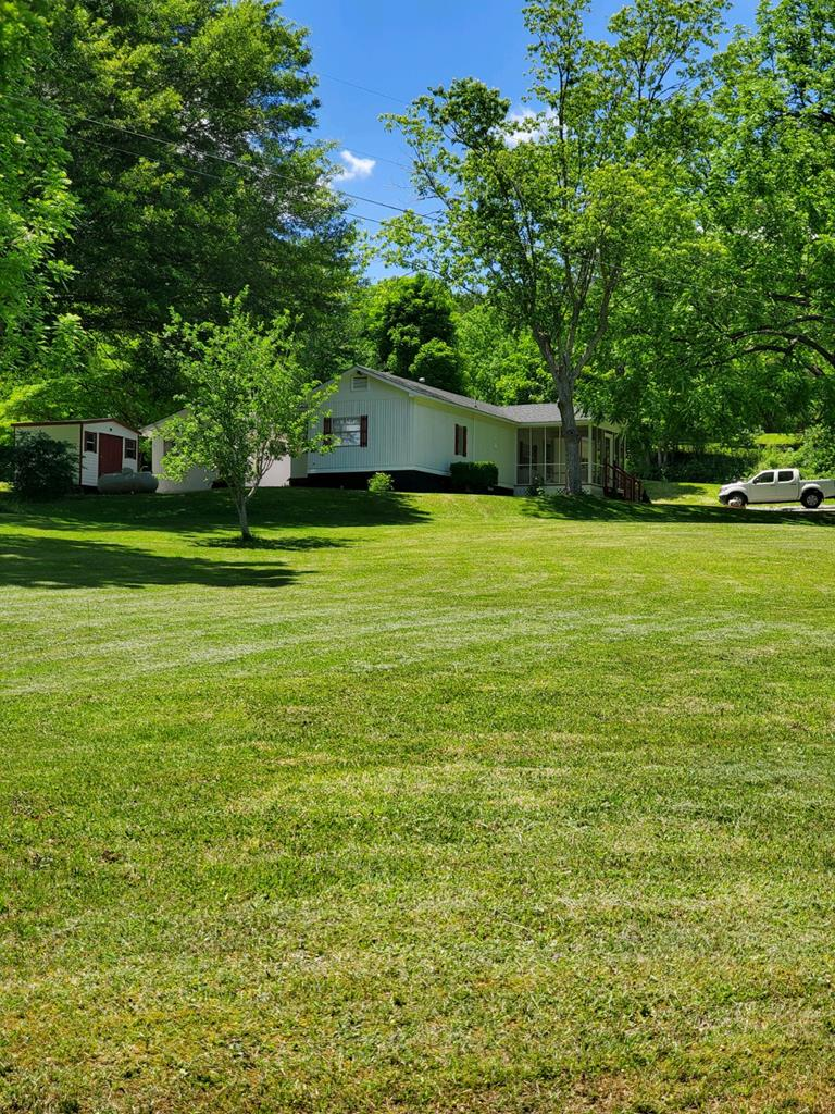 You'll fall in love with this charming home, on 3.1 acres, has 2 bedrooms/2 full baths, living room, dining/kitchen combo, wood floors, washer/dryer area, office/bunk room, porches outside, storage, carport, and two wells, stream and pond area.  Located close to towns of Hayesville and Hiwassee.