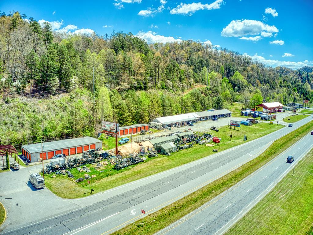 High exposure property with multiple business opportunities and plenty of parking! 18.04 acre tract with approximately 600 feet of road frontage on US Hwy 441 directly across from Uncle Bills Flea Market and the Tuckasegee river in Whittier, NC. Direct, high traffic area flows between Bryson City and Sylva NC with easy access to Great Smoky Mountain National Park and Harrahs Casino! Property features two storage unit buildings with a total of 32 unheated units. Heated warehouse space, broken up into 15 units is currently used as flea market with store fronts. Property also includes 1 large billboard with an active lease. Back of property has potential for residential development