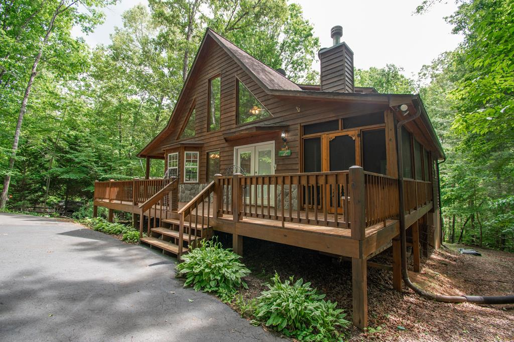 2BR/3.5BA chalet w/circular drive, finished basement & bonus rms has space for a family to live or vacation! Main level has GR RM w/WB stove insert in stone fp, 1/2 BA, laundry & an option for owner suite w/screened porch & balcony.  The loft could be a second living space or owner suite w/jacuzzi tub in full BA & screened balcony.  Finished basement has a good sized family room w/walk out, two bonus rooms, full BA, plenty of storage/closets & mechanical room w/utility sink.  An open & covered porch wraps two sides of the main level from which to enjoy the beauty of the wooded lot.  Storage shed in fenced back yard for your four legged friends.  Quiet area close to Blairsville & Murphy.