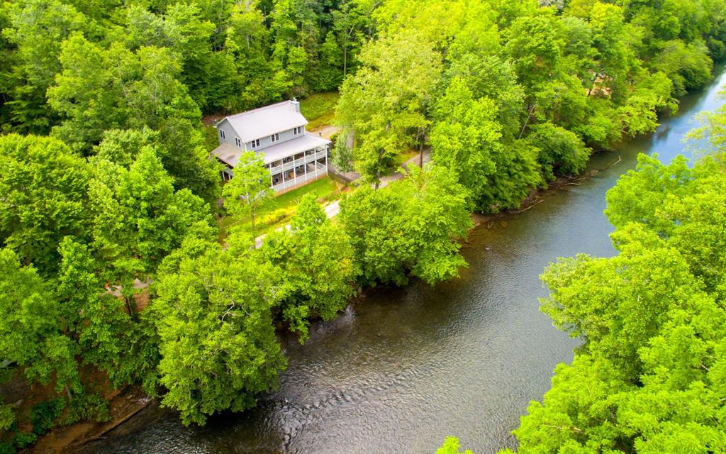 LUXURY ON THE RIVER IN THE MOUNTAINS OF NORTH CAROLINA!! Located on the banks of the Hiwassee River, this quality built 3 bedroom, 3.5 bathroom home offers 2 levels of huge decks to enjoy the mountain views & soothing sounds of the river, a beautiful blend of drywall & wood interior, wood floors throughout, exposed beams in kitchen, stone fireplace, great room with a decorative stone wall, library with built-in bookshelves, office, mudroom, laundry on lower & main level, wine room, hobby room, 2nd living room with wood stove, large master bedroom with private screened-in deck, master bath with a large glass & tile walk-in shower, kitchen with Cambria Quartz counters & stainless gas stove, an