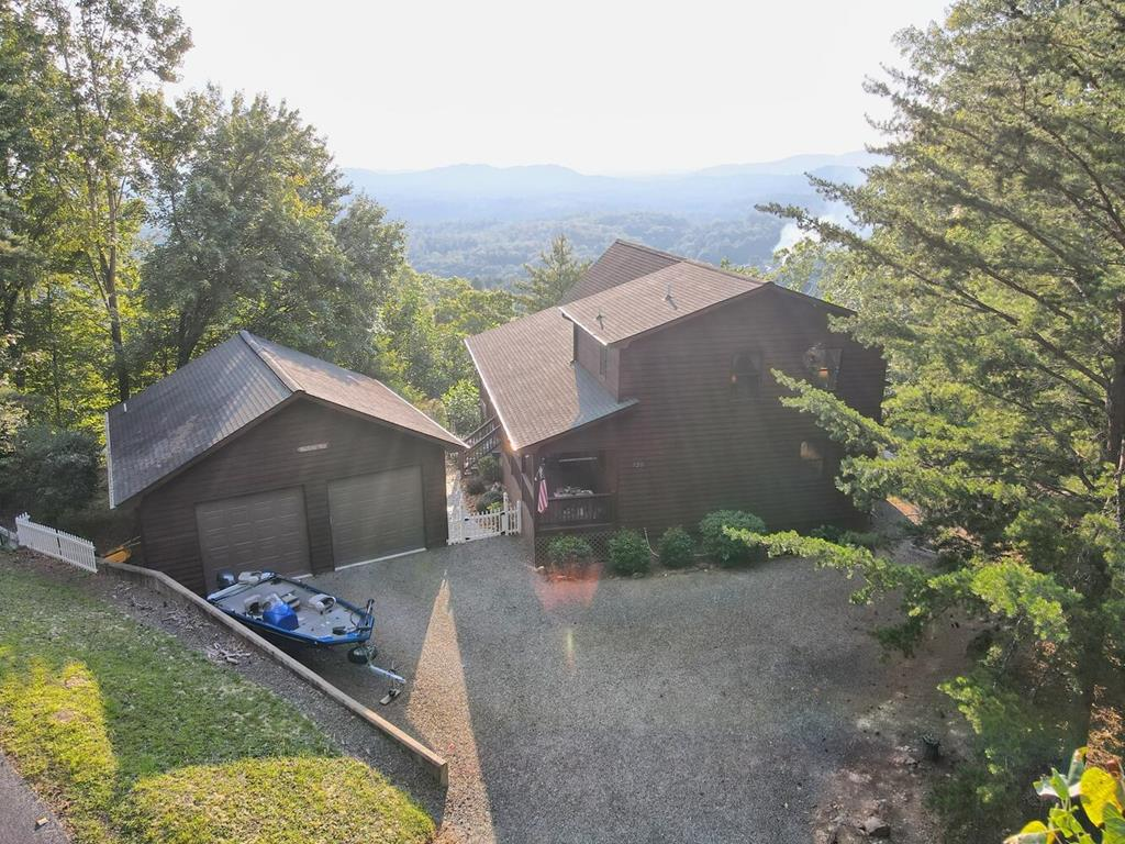 Take Two! Two levels of porches, two car garage, 2 lots, & two-plus levels of delightful living await you in this chalet home with BREATHTAKING LONG RANGE MOUNTAIN VIEWS. Bake and cook in the expansive, open kitchen with granite countertops, brilliant maple cabinetry, & space for family & friends to gather & enjoy the rock fireplace. Main-floor bedroom is perfect for guests or home office space while the loft master suite is your paradise. Boasting an expansive vaulted wood ceiling, a walk-in closet, and full bath just for you. Finished daylight basement includes a bonus room, large recreation room, and your third full bath. Light, airy, move-in ready: just unpack, relax and enjoy the VIEWS!