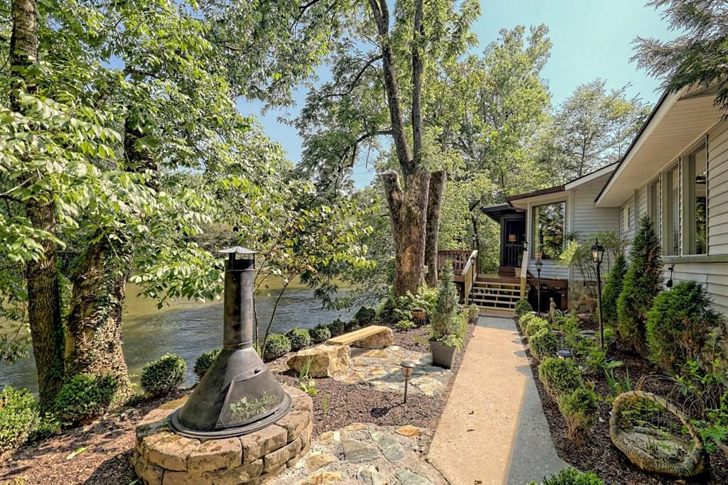 HIWASSEE RIVER DREAM:  You will fall in love with the lodge like interior of this completely renovated riverfront home.  Custom details throughout, from the luxury kitchen and baths to beamed ceilings and solid wood floors.   There is nothing original about  the 3/2 split floor plan with rich warm tones of tongue and grove ceilings and walls.   Over 400 sq. ft of screened porch with vaulted ceiling over looking the river.   The exterior of this home is as inviting as the interior, with professional landscaping, and large breezeway to enjoy the river breeze.     Great location on minutes from historical downtown Murphy.   This home is as amazing as the photos, you will not be disappointed.