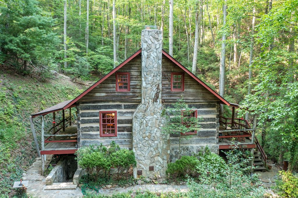Live the mountain dream in this unique custom log cabin on over 15 acres sitting right beside a cascading stream. This one of a kind log cabin was built using hand hewn logs from an 1830's school house and  the interior wood and logs from an 1860's home and barn. The original mantel from the 1860's home hangs over the wood burning fireplace. Hand carved exposed beams were added to the ceiling to be viewed from the main floor and loft. Spruce wood covers the walls and ceilings of the finished basement creating a warm atmosphere. A network of stone pathways encircle the home leading down to the creek. The property also has a large shop/garage with a loft. A must see home that's rich in history