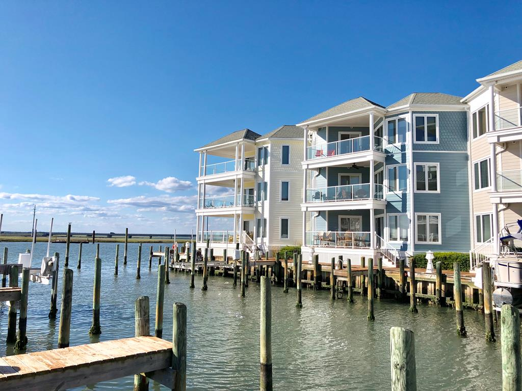 REDUCED WATERFRONT Sunset Bay unit with BOAT SLIP! Gym & Pool on site! Water views from open concept kitchen, dining & living room! NEW Mannington, Luxury Vinyl Plank/waterproof hardwood. Balcony access. You will love the Kitchen cabinets & Island with double sink & dishwasher. Master Suite with bed & comfy chairs facing the WATER VIEW, mirrored his & her closets, whirlpool tub, double sink, tile shower in master bath. Two additional bedrooms with POOL VIEW, nice in size with tasteful decor. Guest full bath. Washer & Dryer. Ceiling fans in almost every room. Open up balcony doors & smell the sea breeze! Successful rental, turnkey ready, conveys FULLY FURNISHED, income helps cover mortgage & HOA fees. Rentals must be honored. Database may convey with fee. Walk to shops, restaurants & park.