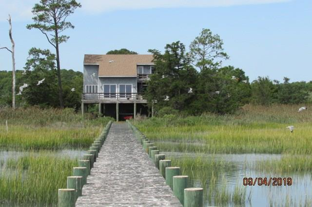 This lovely waterfront home is a must-see. It brings you the best of the seaside. Use it for vacationing, retiring or your virtual workplace.  Reside high above the wetlands, and enjoy unobstructed views of the beautiful marshland, Cedar Island and the Inter-coastal Waterway from the decks, dock, or yard. Hop in your kayak or boat from the deep water (7 at low tide) dock to investigate the wonders of this spectacular eastern shore peninsula. And a large county-owned boat ramp is just up the creek. The bright and open great room with vaulted ceiling is the ideal place to hang out with the family while watching the sun rise in the sky. 3 bedrooms, 2.5 baths and large kitchen and great room, providing the perfect place to enjoy quiet evenings. Dock your boat with 7 ft at low tide.