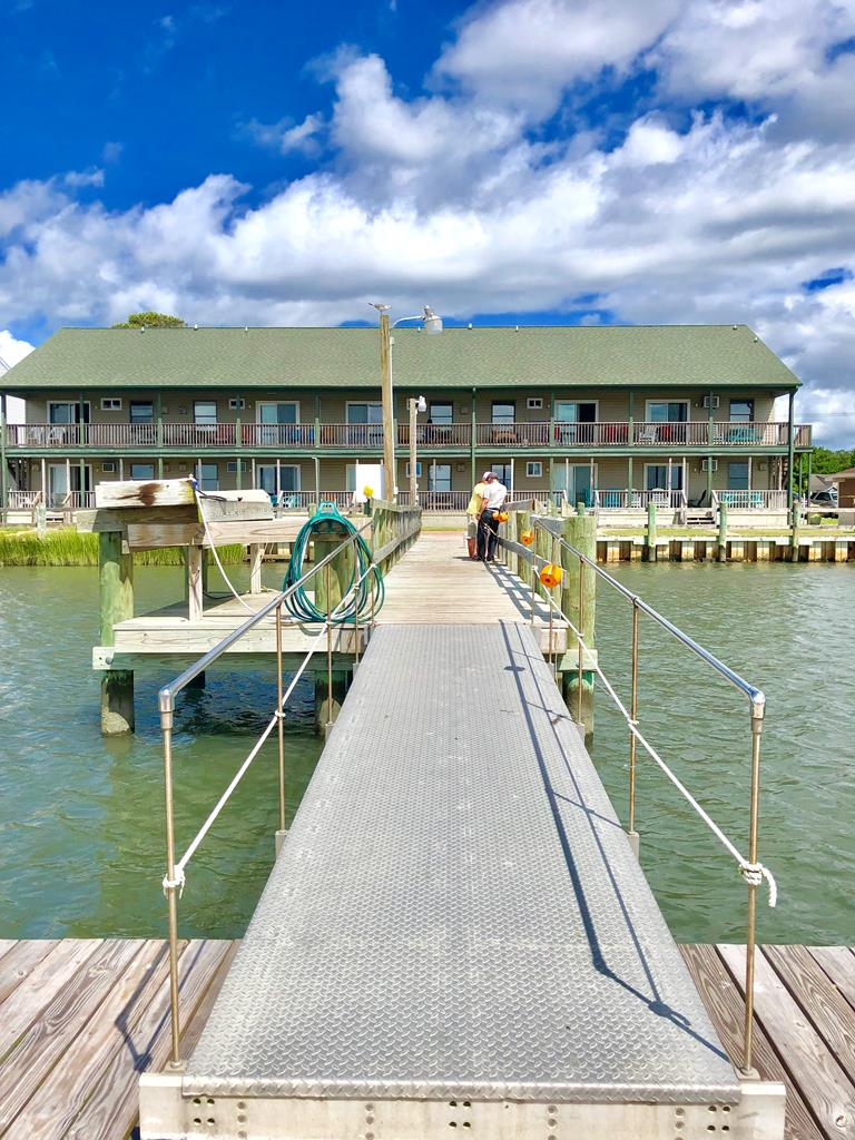 WATERFRONT totally renovated condo with BOAT SLIP! Island life at it's best! Located on the second level, amazing views of lighthouse & Channel. Two nice size bedrooms with carpet & ceiling fans. Great open space for kitchen area, dining & living room with the incredible WATER VIEWS! Glass slider in living room leads out to covered open porch for additional sitting & dining space, watch the sunrise over Assateague Is with your morning coffee! FULLY FURNISHED! Tile flooring in the kitchen & living room. ENJOY THE PIER...like to crab & fish? Do it right in your back yard! Pier & slips recently upgraded. Grounds are meticulously well kept with bbq grills. Laundry room on ground level. NEW 4 years ago: sheet rock, plumbing, kitchen, bath, flooring, electric & MINI SPLITS throughout!
