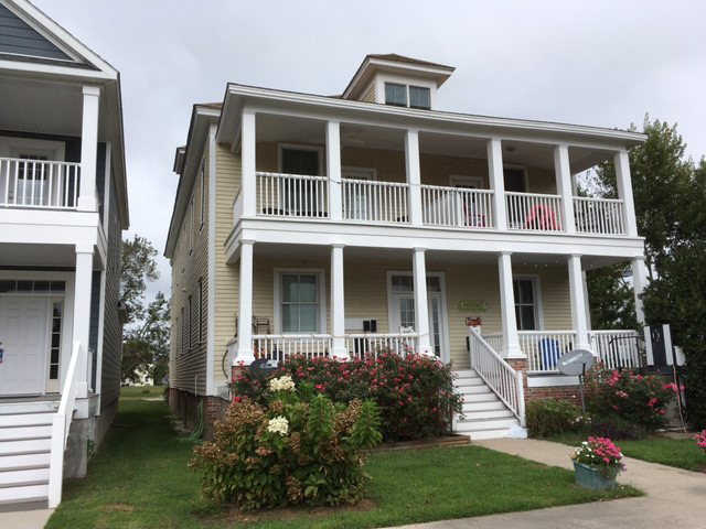 Best price on Cape Charles condo only 3 blocks to the beach!! Only 4 condos in this beautifully renovated historic building. This unit is on the first floor with light filled south facing unit with covered porch overlooking Cape Charles Central Park. Condo has 10 foot tall ceilings, beautiful pine floors, granite counter tops, 2 gas fireplaces,  handsome moldings, tall windows, and open concept floor plan. Master suite with gas fireplace has ample closets and private bath with large soaking tub and separate shower. Condo has lots of storage with additional storage compartments in the basement.. T.