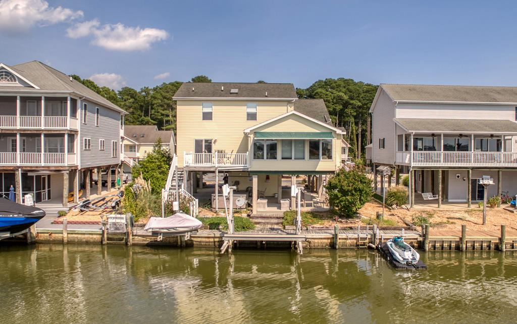 Beautiful Canal Front Home in Captain's Cove Golf & Yacht Club offers expansive Views of the Chincoteague Bay & Wetlands - Relax w/your morning coffee while watching the Herons & Egrets dance over the water. This Custom Home comes in at almost 2400 sq ft, and has 3 spacious Bdrms, 2 Full Baths, a Family Room, Loft, AND an ELEVATOR! You'll be welcomed Home by Soaring Ceilings & a wonderful Wall of Windows facing breathtaking Views. Enjoy your Water Views from the huge Deck or below on the Boardwalk - and no worries, your Views will never be obstructed!s directly across the Canal! This Waterfront Dream Home also has an Aluminum Boat Lift & Aluminum Jet Ski Lift. Just imagine the stars from your Hot Tub (conveys at no add'l value). Newer HVAC in Main Living Area. Amazing Cove Amenities YOURS!