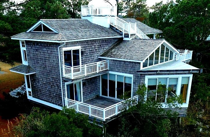 """Richard Vesely-designed masterpiece in a simply gorgeous community! Magnificent custom-built waterfront home in the Salt Marsh community on Chincoteague Bay. Vesely's prestigious design work is evident throughout, taking advantage of the spectacular vistas with plenty of room for family & guests. Step-down """"gathering"""" room with built in storage and massive windows to watch the awesome sunsets and wildlife in the marsh, 3 large bedrooms with en-suites with their own balconies, & den/office area. Beautiful woodworking throughout, separate dining room and living room with stone fireplace, built in lighted display shelving, hardwood floors, screened porch (14' x 12') off dining room. Kitchen is chef's dream with massive pantry, storage cabinets w/many pull out features plus wet bar.  560' pier"""