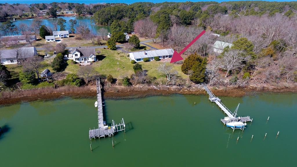 Deep Water!!! 1 story 4 bedroom waterfront home located on a stunning 1acre lot overlooking Hungers Creek. Hi elevation & about 6 to 8 feet at low tide. That is very hard to find in Northampton county. The dock offers a heavy duty (approximately 9000 pound) boat lift, running water with sink & fish cleaning station &. electricity. Near the dock  is a shed with an overhang roof. This custom built home is in very nice shape. It may need cosmetic work. The living room has large windows with lots of natural light over looking the creek and a  brick wall fireplace that was converted  in to a pellet stove. Spacious kitchen open to the living room. Of the kitchen is a large den with custom build ins overlooks the water. Master suite, large laundry room and two attached garages.