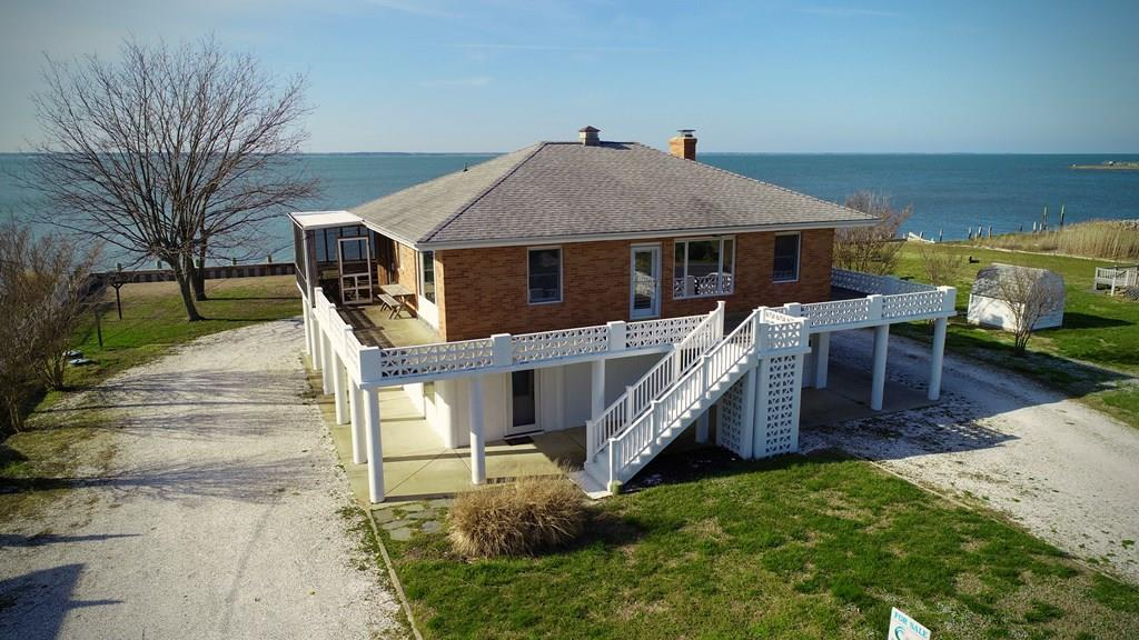 "SOLID CHINCOTEAGUE BAY FRONT HOME WITH A LARGE LOT! HALF AN ACRE !! Waterfront ""with space"" is what you get with this ""Unique"" Established Island Vacation Home. A Large Open Floor plan on both levels .  A great sense of Space and Wide Panoramic Waterviews from every room! Large wrap around Deck.  Two Levels and Two large Family Rooms make it great for enjoying family and having privacy at the same time.   Some features further include an Attached Garage, A Cozy Living room  Fireplace,  Large Screened Porch off the open deck, Private Pier, Outdoor Shower, Two zone heat and a/c. Oak Hardwood Floors  throughout. Large wide Bulkheaded High Lot.  A great for home for entertaining inside as well as outside. An established vacation rental selling fully furnished, equipped and turn-key."