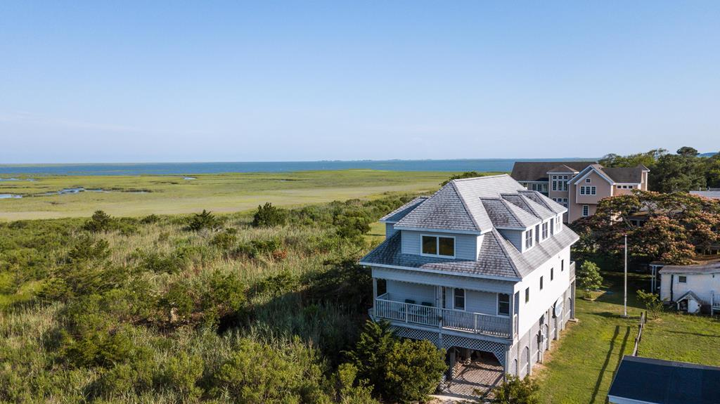 Nantucket style Coastal Cottage in pristine setting on Virginia's Eastern Shore overlooking Mockhorn Bay on Seaside.. Enjoy wide expansive views of the marshes and Mockhorn Bay. Direct access to barrier island beaches & fishing from Oyster Harbor. Natural setting in quaint seaside village of Oyster. Home was owned and built by a custom builder..custom craftsmanship throughout. Open concept floor plan w/ plenty of natural light thru out. Beautiful white oak floors & handsome staircase. Large family room area & master suite on 3rd floor has stunning views. Lots of storage space indoors & out. Plenty of outdoor living area.. expansive decking and covered porches. Workshop on ground level. Wake up every morning to a beautiful sunrise. Minutes to Cape Charles beach, restaurants and shopping.
