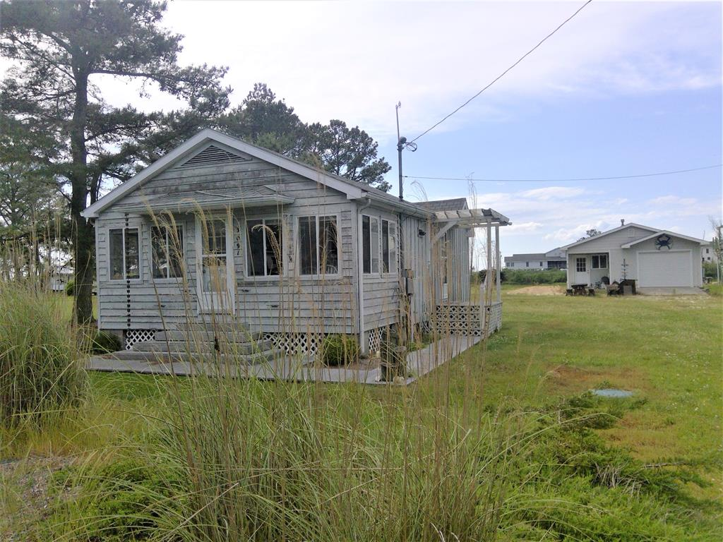 """Location Location Location. Enjoy the breezes off the Chincoteague Bay with this location. """"Cute as a button"""" is all you will be saying when you see this 2 br beach bungalow that conveys with a detached 2 car garage and pier on Fowling Creek. Bungalow features vaulted ceilings and great open floor plan. Enjoy the light that streams in. The wind whistling in the Pines and the Bay breezes will be a constant reminder that you are on Island Time! The detached garage has TOO many pluses to mention. COME SEE FOR YOUR SELF. Crab right off the pier, buy a kayak, take up fishing!"""