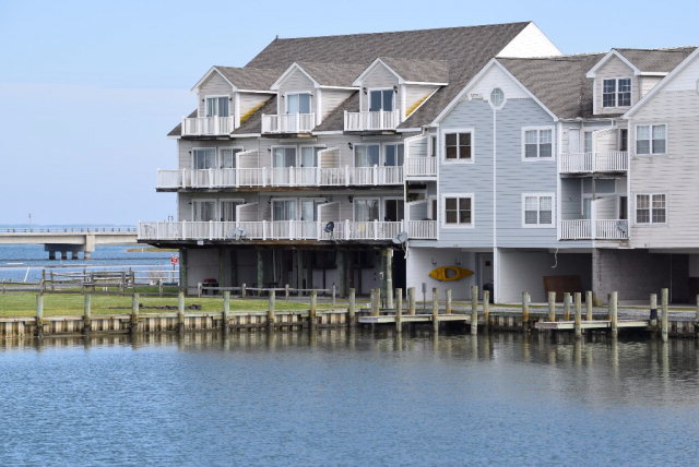 This three-story townhome with boat slip is located on a private island for the use of Marsh Island homeowners and guests only. Private balconies on all three levels, 2 x 6 exterior framing with parking and storage on the ground level. Two-zone heating and cooling and lots of storage space. The westerly facing home allows for private viewing of sunsets across Chincoteague Bay, fireworks from the carnival grounds and rocket launches from the NASA Wallops Flight Facility GSFC. This home comes completely furnished and move-in ready with two queen beds and two sleep sofas. Only minutes from the beach and all of the amenities of Chincoteague and Assateague. Homeowners have the private use of all common areas including fishing, crabbing, and boating from the shared dock. includes boat slip # 4