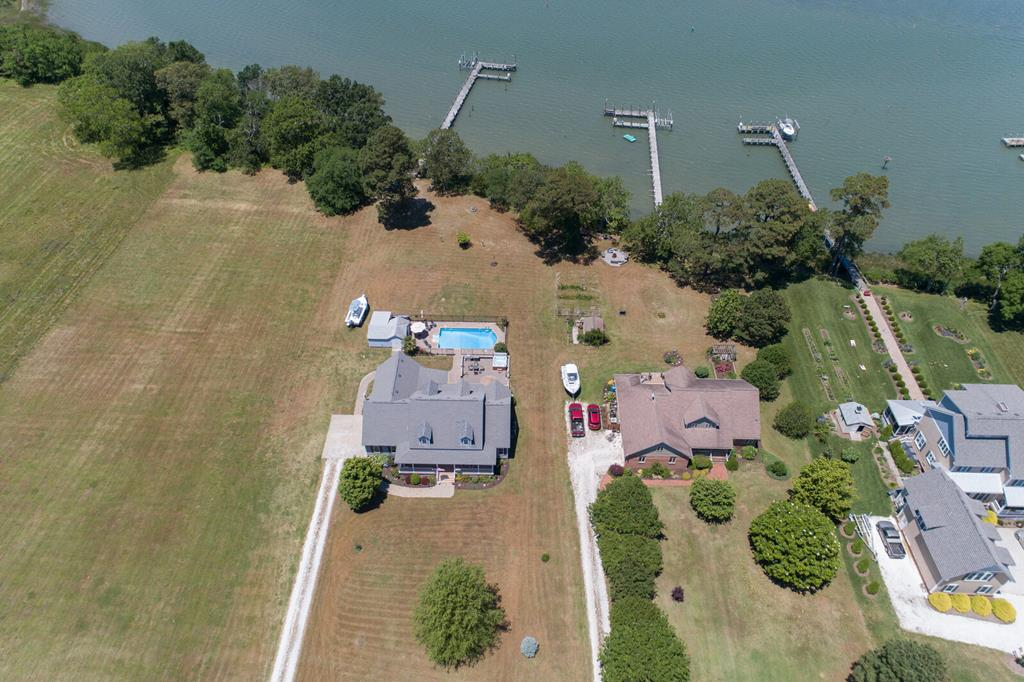 Best boating water on the Eastern Shore!  1.5 Acres located in Wilsonia Harbour has deep water on Hungars Creek at the mouth of the Chesapeake Bay.  Wonderful 2500 SF home has 4 bedrooms, 3.5 baths, hardwood and ceramic floors, 1st floor master bedroom + 2 more DS bedrooms, large kitchen with eat-in area, SS appliances, opens to family room w/ gas fireplace, dining room and bar are.  Circular stairway leads you to 2nd floor loft, full bathroom, bedroom and flex room.  This home is made for family and entertaining!  The most relaxing back porch with ceiling fan awaits you to enjoy the evenings. Screened-in porch area with picnic table for eating those delicious steamed crabs!  Beautiful stone patio with sitting wall, hot tub, in-ground pool, pier w/electricity & boat lift; no flood insuranc