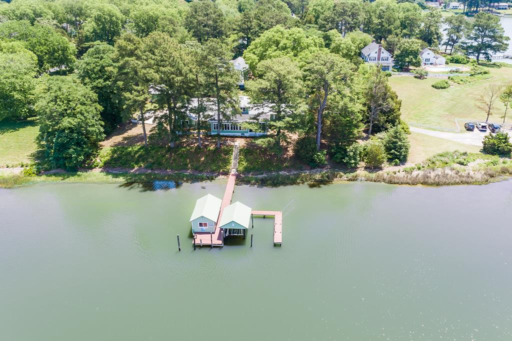 Incredible opportunity to own one of the finest Eastern Shore deep water properties, on a private in-town setting. Situated high above Onancock Creek, this home has water views from every room in the house. Enjoy four seasons of spectacular water views and your own double dock and boat house. Deep water allows for large cabin cruiser or sailboat docking with deep water out to the Chesapeake Bay. The open floor plan is perfect for entertaining guest, and includes a private owners wing. The original part of the home was a circa 1920s SearsRoebuck home, and totally remodeled in the early 2000s. Enjoy your favorite beverage and water views from the southern style screened in porch or open deck area. This 1 acre lot is filled with mature landscaping and has room for boat and RV parking.