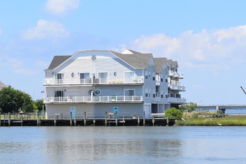 Beautiful VIEWS abound from this lovely waterfront Townhome overlooking the Marshes and Chincoteague Channel. Gorgeous Chincoteague Island Views. Deep Water access , Great crabbing & Fishing. Great for Kayaking , boating, and more. This fully furnished townhome is an established vacation rental and will convey turn-key with immediate income. Marsh Island is quiet, peaceful and away from the island's hustle and bustle.  This unit offers parking underneath the unit, an enclosed stairway to the first floor where you have an open concept living room and kitchen with amazing views.  Large Balcony! (half bath also) Go up another level and you have a bedroom and full bath and large private balcony . Up another level and you have a massive sized bedroom (enough for several beds) and a balcony.