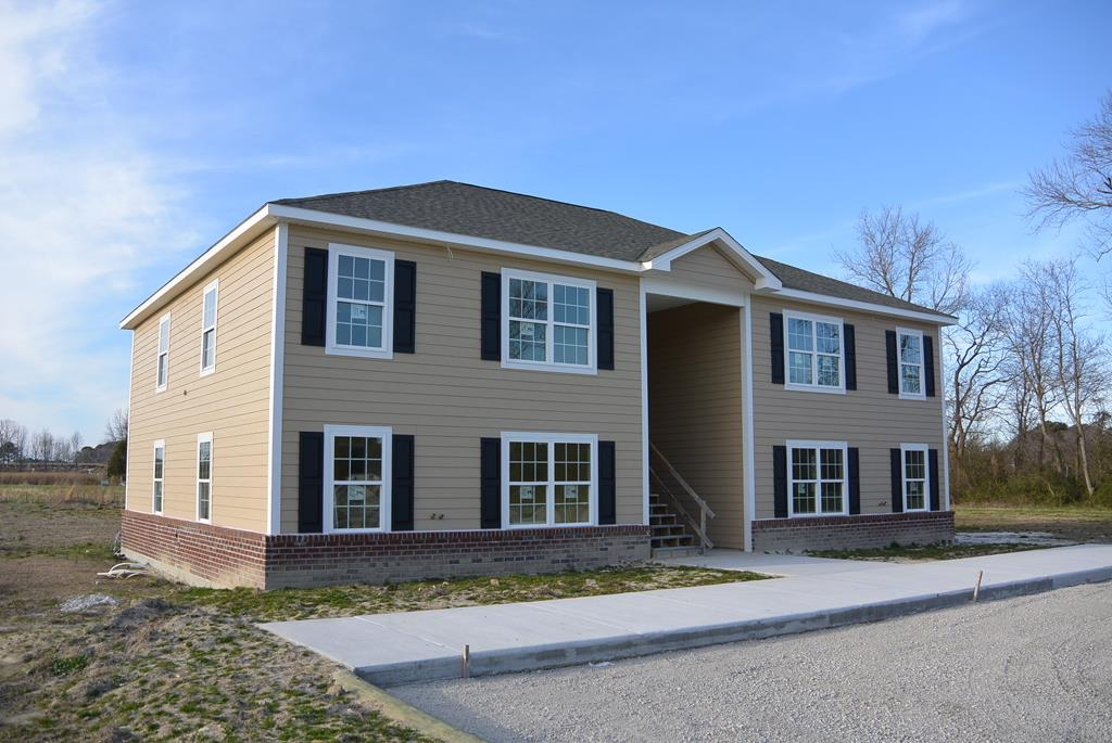 Residential Investment Opportunity: 4 unit apartment building on a one acre in town lot. Each unit has 2 bedrooms, 2 bathrooms, 2 units first floor, 2 units second floor. The building is constructed as a 4 unit condominium and is offered as a whole building for a limited time only. Priced as complete with CO. Additional multifamily lots available for developer/builders. See floor plan for the building and plat under document tab.