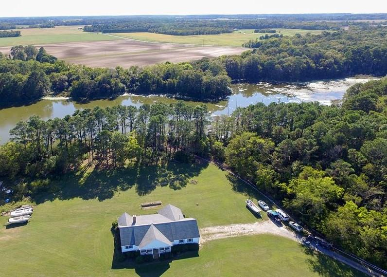This beautifully crafted ranch style home was custom built to withstand the test of time. Solid well built home with total 1st floor living, built by local builder Tommy Arnold using 2 x 6 framing throughout. it is located on a 5 acre lot, which overlooks a freshwater pond, teeming with a variety of freshwater fish. Community dock, easy access to barrier islands, saltwater fishing and bird watching. Custom kitchen, spectacular wood burning fireplace, Rinnai hot water heater and Buberus boiler heat. Spacious living room leads out to the screened porch, offering lots of outdoor living space. Attached 2 car garage, large office space, full house length attic for storage. Detached metal building, is perfect for boats. Abundance of birds and wild life. Close to shopping and restaurants.