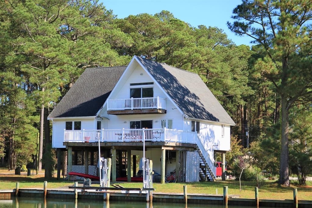 Captains Cove is a desirable waterfront and golf course community on Virginia's Eastern Shore with a limited availability of waterfront homes. This 2000+ square foot home features an open floor plan with 2 bedrooms and 2 full bathrooms on the main living level including a large owners suite with private deck access. The living room boasts beautiful wood floors and large sliding decks leading out to a huge deck with amazing views, while the kitchen and bathrooms feature tile floors. The large kitchen and dining area offers ample cabinet space, a large breakfast bar and access to a private loft/bonus space. The second level features two more spacious bedrooms (1 with a private deck) and a third full bathroom. This property is being sold turn-key if you want as well.