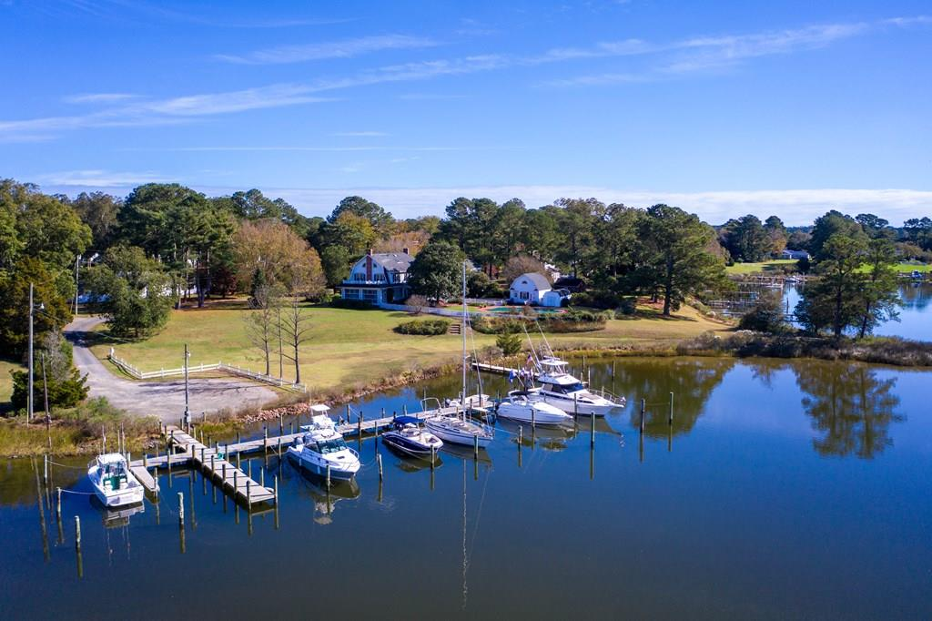 Very unique property available in the town of Onancock with its own private 14 boat slip Marina! The property also features a large in ground pool with views overlooking the creek and plenty of backyard space, perfect for kids or entertaining. Accessible from both the backyard and living room is a screened in side porch where you will witness some of the most beautiful sunrises and sunsets you've ever seen. Inside this Tank Cropper built home you'll be welcomed by a spacious foyer, custom wainscoting and trim work in nearly every room, 2 fireplaces (gas or wood burning), and a sun room with lots of natural lighting. Just a short walk from town, this home is conveniently located near the area's most popular restaurants, stores and the town harbor.