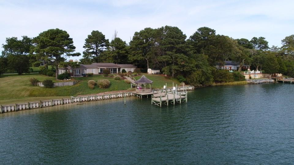 """This gorgeous 4633 sq.ft. custom waterfront home offers the """"best of both worlds"""". Huge Chesapeake Bay views and great boating ! Located at the mouth of Nassawadox Creek with protected boating water. Bring on the QE2 as has 10' of water at the dock. Contemporary home with total 1st floor living. Windows galore offer dramatic waterviews from almost every room. Totally remodeled with granite & tile counters, custom cabinets, built-in shelving, wet bar, plantation shutters and hardwood floors. Huge screened porch overlooking the water, great for entertaining. 4 bedrooms, 4 full baths in a split living floor plan gives the option of an in- law or guest suite and handicap accessible. Great dock, like- new boat lift and a gazebo to enjoy the amazing sunsets over the Bay."""
