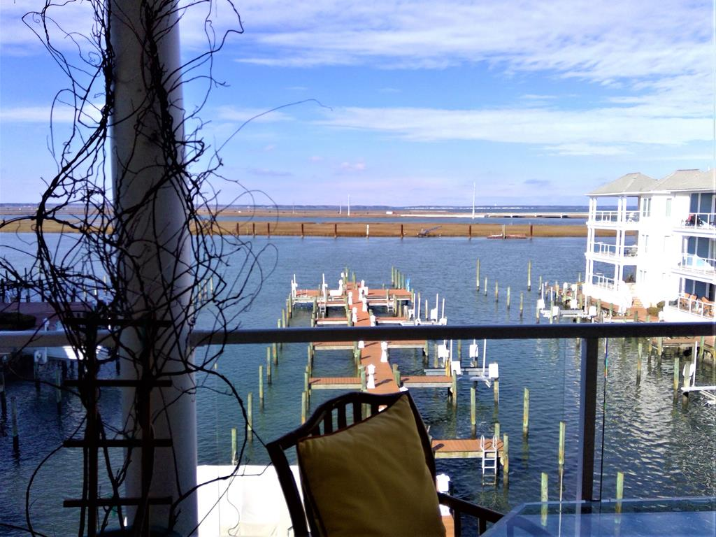 Luxurious Waterfront Condo boast views of the Chincoteague Bay. Catch the year round beauty of the Famous Chincoteague Sunset from the west facing balcony. Property would make an excellent vacation rental. Living room offers wonderful high ceilings, open floor plan w gorgeous water views. Professional detailed, kitchen features black Emerald Pearl granite, maple spice cabinets w custom wood lazy susan, pull out shelving, professional grade appliances and range w warming drawer & pseudo oven. Main bedroom features floor to ceiling windows, entrance to balcony, custom on-suite w luxurious steam shower, separate vanities with storage galore & his/her closets. Amenities include pool, fitness center.  Unit conveys with Boat Slip # 40 and storage shed. NEW HVAC & heater installed in late 2020.