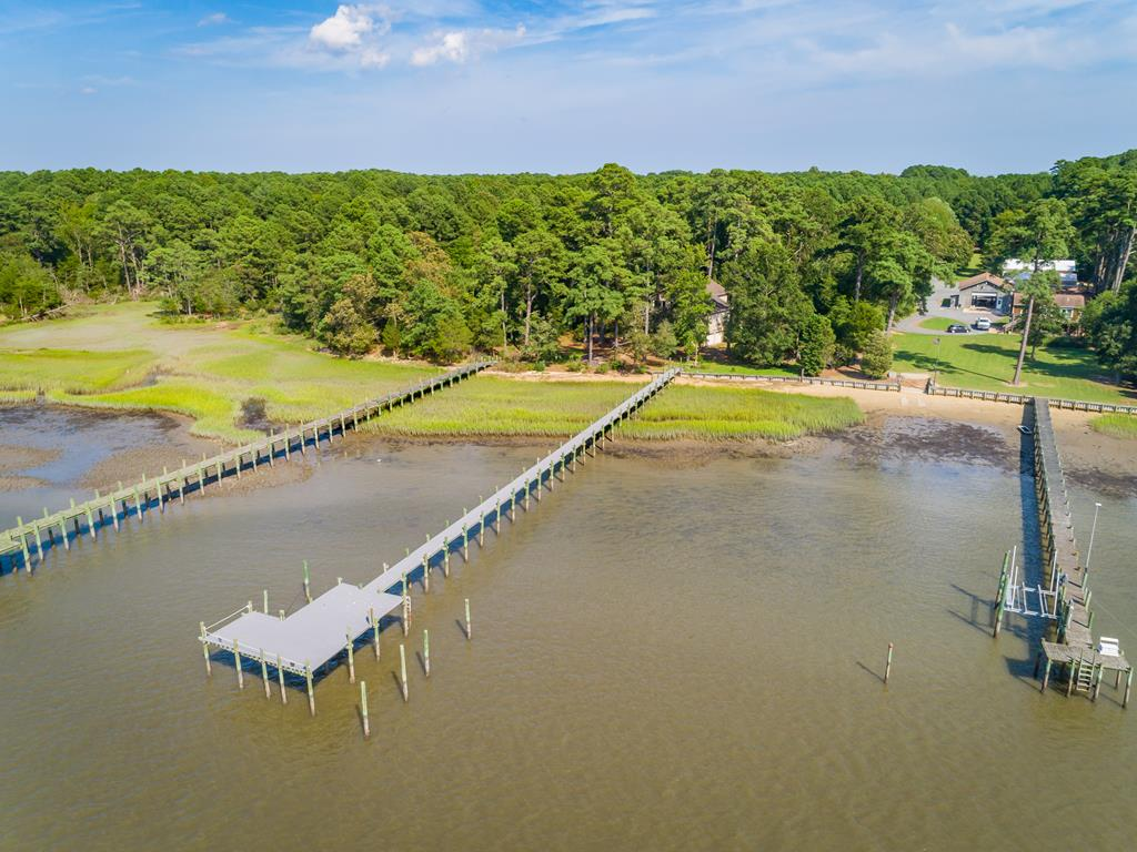 This is a marvelous 2500 square foot custom built home on The Great Machipongo River! Situated on a total of 6.4 acres which is also a recorded 4 lot subdivision which gives you multiple opportunities. The house sits on 1.88 acres with 146' of waterfrontage and gorgeous new deep water dock. The dock is equipped with electric and water and ready for you to pull  your boat up from a day on the water. Enter the home from the large garage with ample room for a workshop and then hop on the elevator to get to any level in the house. The first level features an open floor plan with a gas log fireplace and a fully customized kitchen with prep station and cabinets galore. Also a laundry room, full bathroom and large bedroom. Upstairs is two more bedrooms and another full bath. 4 decks and balconies