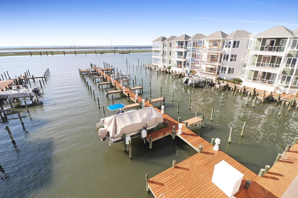 This new Sunset Bay listing is situated on on the 3rd floor overlooking the marina and out to the Chincoteague Bay. The moment you enter this villa you're greeted ample amounts of natural light. The spacious open floor plan starts with a huge kitchen with a ton of cabinet and counter space and leads to the dining area and living room. The sliding glass doors leads out to a peaceful deck looking out over the sunsets. The large owners suite has a access to the waterfront deck. It also features two closets and a bathroom with dual vanity, tiled shower and jetted tub. There are two more large guest bedrooms and another full bathroom. Call today, Sunset Bay Villas Sell Fast!