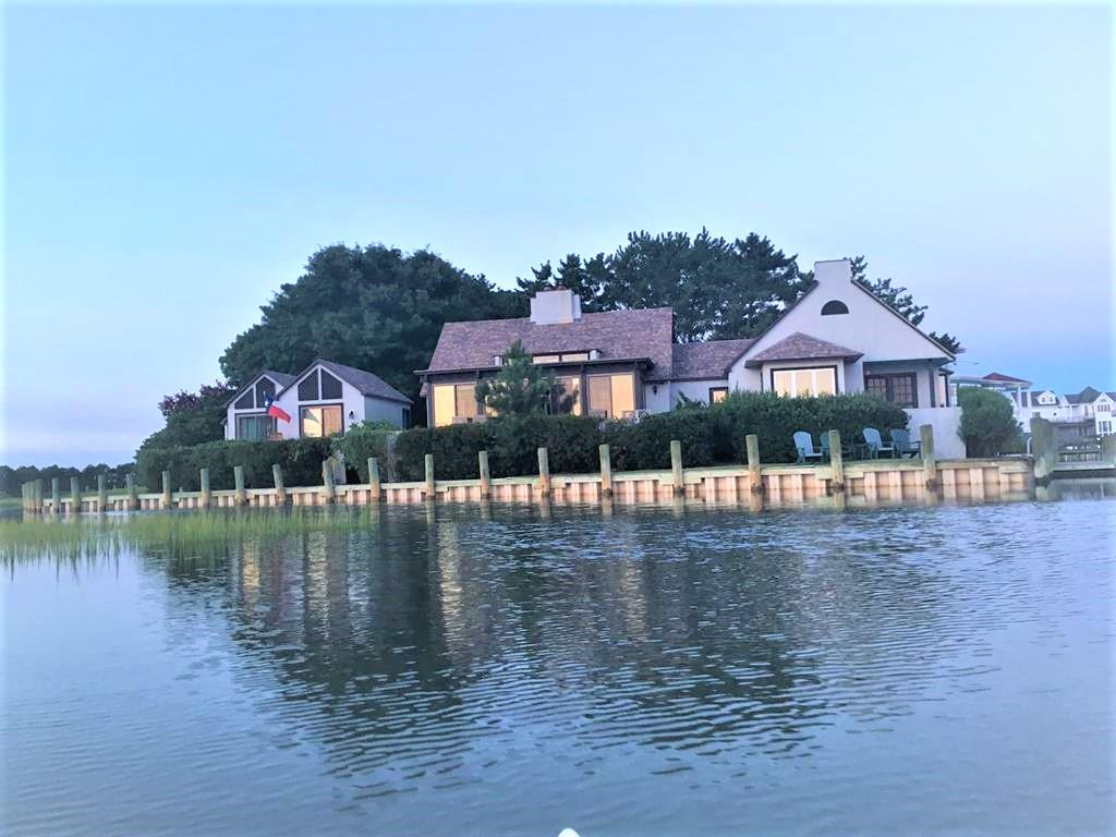 Rare Island find! Stunning waterfront home & guest house on Assateague Channel with incredible view of the lighthouse. Being at the confluence of 3 creeks, the birding is extraordinary. The Main house offers vaulted ceilings, sky lights, terracotta floor to open concept with center wood fireplace on the living room side & range on the kitchen side/dining space that flows into the solarium giving you breathtaking views from every angle! Open decks on both homes. Two lovely bedrooms with hardwood floors, one with private covered balcony. Full bath with double sink vanity. Guest cottage offers a full bath, two bedrooms, one with private balcony & half bath. Surrounded by trees, water & bamboo for the ultimate privacy setting. Premier, established rental. You have to view to appreciate!