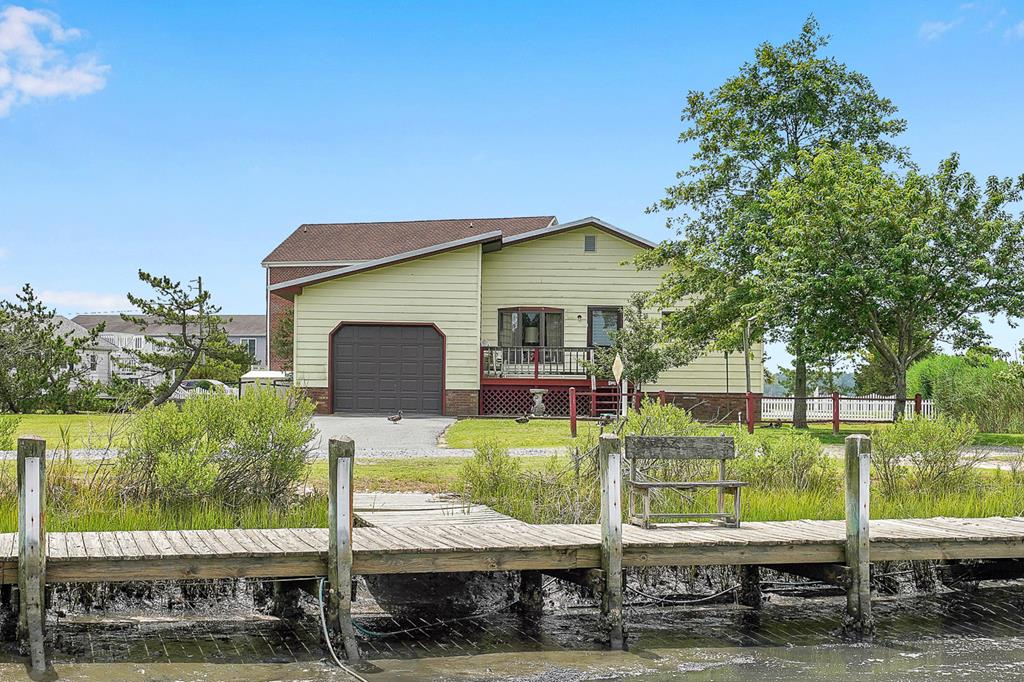 Waterfront Rancher with Dock! Take a look at this cozy 2 bedroom 1 1/2 bath, ranch style home which is situated on over a 1/2 acre lot. This Chincoteague charmer is nestled in a quiet neighborhood on a dead-end street. It features a spacious living room, dining room, kitchen w/breakfast bar, and front porch. Relax on the covered rear porch which overlooks the huge yard. The attached over-sized garage is perfect for additional storage or a great place to keep your boat! So many possibilities with this property as a year-round residence or investment unit. Great central location within close proximity to Memorial Park, bike trail, wildlife refuge, Assateague Island, restaurants & shops.
