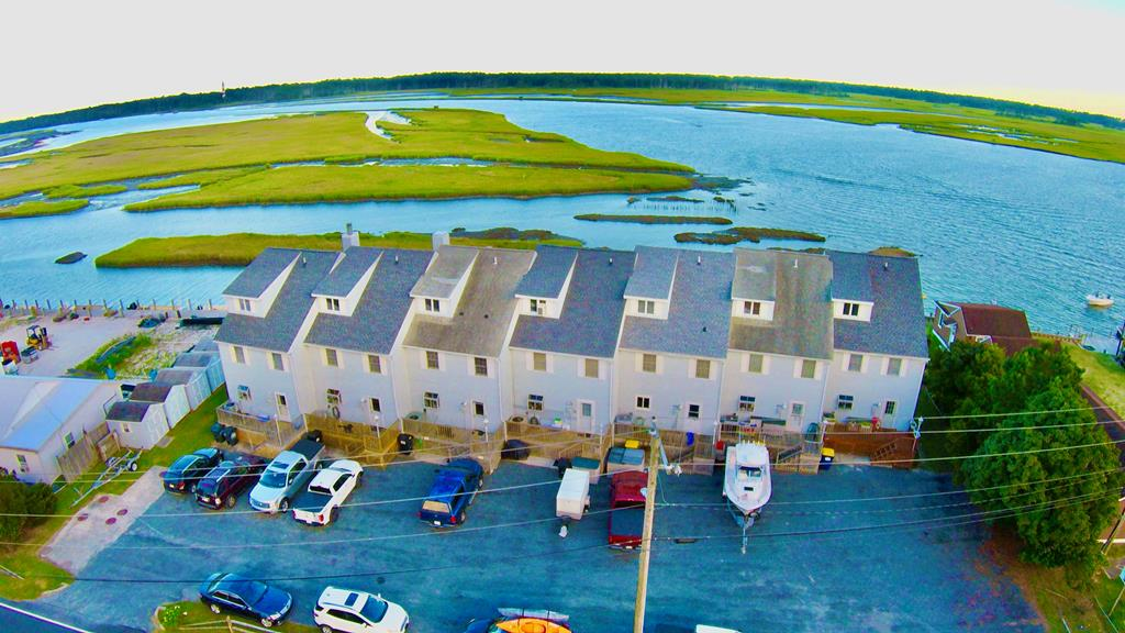 THIS IS WHAT CHINCOTEAGUE IS ALL ABOUT! WATERFRONT on the East Side where you can view the Lighthouse, Amazing Waterfront Vistas, Sunrises , The Ocean in the distance, The ponies grazing on the marshes, and the action during the Annual Pony Swim.  This place is therapeutic and will take your breath away! this PRISTINE unit is in tip top shape being it has Original Owners. It has never been rented, has a brand New Roof, New Floors taken down to the studs. New Kitchen & Appliances, Newer HVAC, Newer Septic , And More.  You get 25 FEET of DOCK to put your very own boat, wave runner, or paddle board. HUGE THIRD FLOOR BONUS ROOM. (makes a great suite). Town launching Boat Ramp is just a few doors down. Conveys furnished . Dues are only $600/year.   You can't go wrong with this place! Paradise!