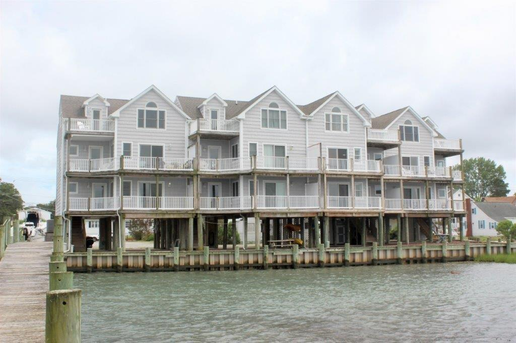 Spectacular Sunsets and breathtaking views over the Chincoteague Bay! This 3 bedroom, 2  bath townhome is nestled along the banks of the Chincoteague Bay and is within walking distance of Historic Downtown Chincoteague. First floor offers Full Bath & 2 bedrooms, one with a deck overlooking the waterfront. Second floor boasts an open floor plan with living room, dining area, half bath, laundry area, nicely appointed kitchen, and a 2nd floor deck for enjoying beautiful sunsets.  Third floor large master suite with a deck and a view overlooking the Bay, and a master bath with shower and a whirlpool tub. For the boat enthusiast a shared pier and your own boat slip. Many updates, freshly detailed and painted, new HVAC units, new roofing and significant updates on all 3 decks.