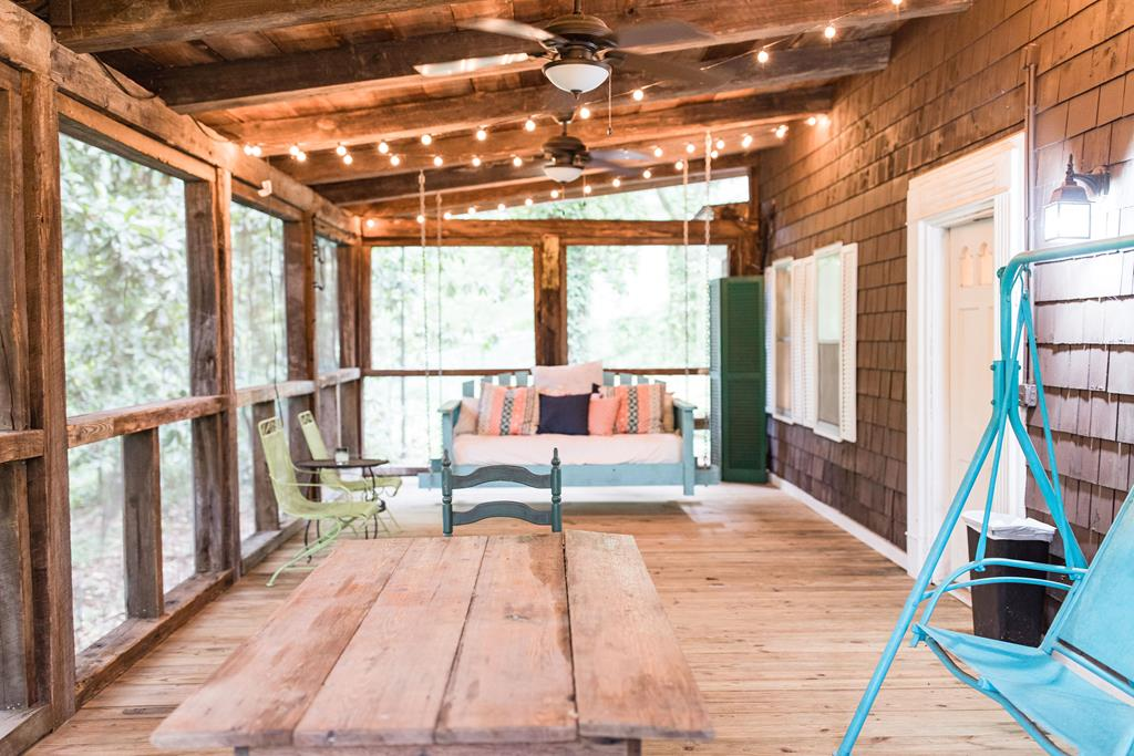 "SCREENED -IN- PORCH is all I have to say!  Beautiful real beams, a big porch swing, and plenty of space to entertain.  The porch and location will sell this rustic-looking cabin/cottage of a home.  The home is surrounded by trees, and less than 1/2 a mile from campus.  Original hard wood floors throughout,  wood burning fireplace, and the original kitchen cabinets are adorable.  The seller has updated the bathrooms, added a new bathroom downstairs, added new kitchen counters, new lighting in some of the house, & the new porch.  Seller also put in an a new  ""old tin roof""   A MUST SEE!"