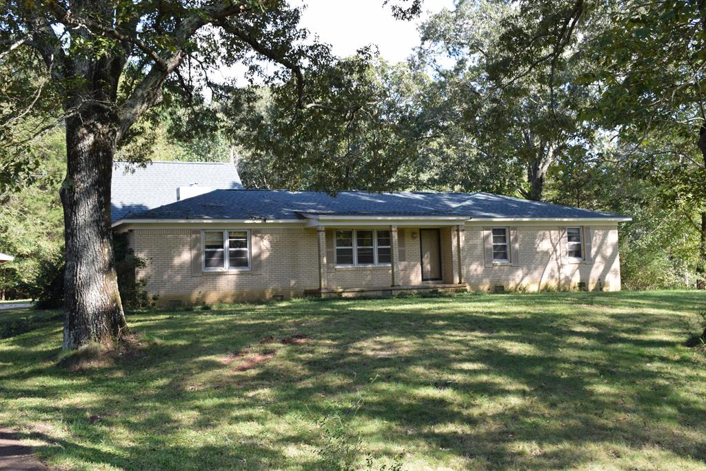 Don't miss out on the best of both worlds. With a heavy tree canopy of mature oaks and a beautiful front yard, this 19070s ranch style home in the Oxford City Schools offers country living with peace and quiet coupled with being only minutes to town. Large rooms and beautiful yard and trees create such potential for this country estate. Manicured grounds with front and back porches create endless entertaining opportunities. The loft with spiral staircase above the living room offers a beautiful place for an office or play room with large oversized windows looking out into the woods.