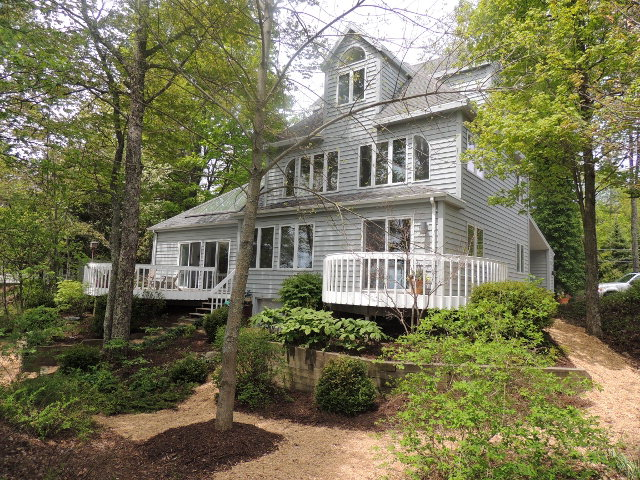 Majestic 2.5 story beach house.  Pickled oak flooring throughout; Corian counters; open floor plan.  Placed on a wooded lot so that you have privacy from the road as well as the beach. 165 feet of sand beach with a small creek running through the property.  With a contemporary design interior, this home is unlike anything being offered in this prestigious community. 2nd floor loft offers even better lakefront views. 3rd floor could have a multitude of uses.  Strategic placement of windows allows the natural light to enter from all directions; with the views of the water and the woods the feeling of sitting in the middle of nature prevails.