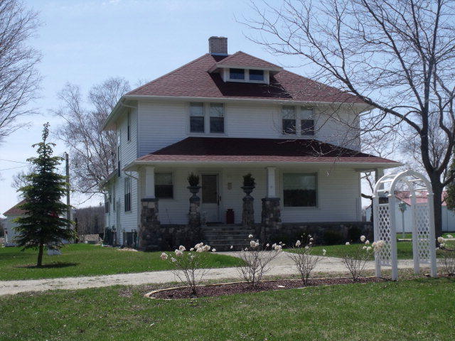 American Foursquare home built in 1911 completely updated with woodwork, cabinets, built-ins and crown molding preserved. Maple floors throughout, open staircase, six panel doors, eat-in kitchen plus snack bar, great pantry, stone floor in kitchen and pantry, enclosed back porch, open front porch, balcony off upper bath.  Outbuildings include: 10.6 x 9.6 potting shed, 22.6 x 17 studio, 26 x 70.6 2-car insulated garage plus rec room with bar and wood stove, 2 heated workshops, 72 x 45 metal pole building.  Also a silo, fountain, fire pit, and power hook-up for an RV.  Part of the 20 acres under cultivation.  A Must See!