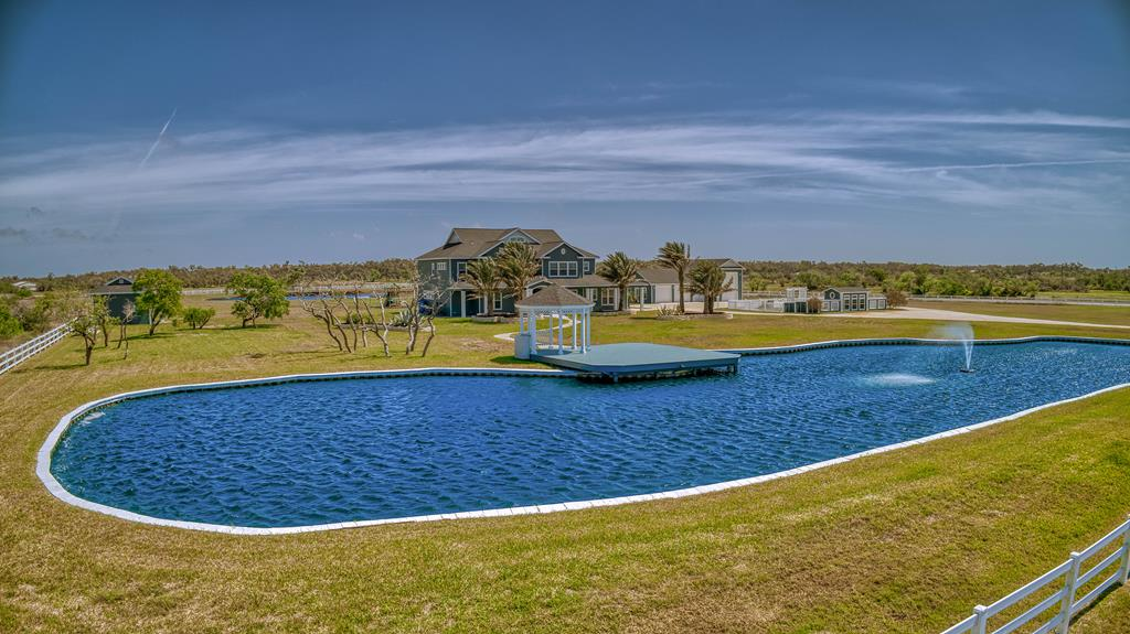 Extraordinary acreage home w dramatic style & creature comforts. Over 7.5 acres of beautiful green pastures, two aqua blue ponds, gazebo & deck create an outdoor living space that's fun & inviting. The ground floor of this estate style home boasts soaring ceilings with exposed natural wood beams, gorgeous tile floors, panoramic views of your acreage and a gourmet kitchen. Host a crowd at Thanksgiving & entertain them in your private media room. Also on the main level is a formal dining room, offices & exercise room or game room. The master retreat is on the 2nd level & it's every bit as luxurious as you can imagine. An expansive abode w private lounging area, a jet tub, walk-in closet, sperate shower & private balcony, you'll never want to leave. Guest bedrooms & bathrooms on this floor are generous in size & all have views of the grounds. A detached storage area is a great workshop, the detached 4 car garage has room for a boat or R/V. The dog grooming kennel and dream retreat.