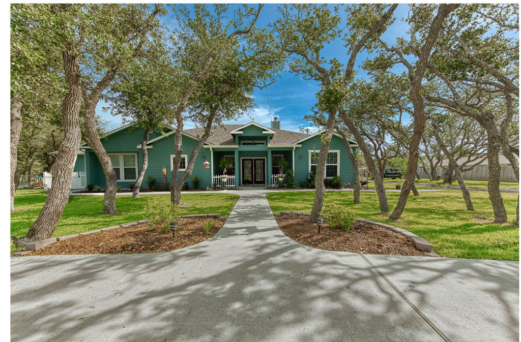One of a kind Rockport home nestled amongst hundreds of large Live Oaks on 3+ acres. A spacious master bedroom& bathroom w large walk in closet, soaker tub, beautiful walk in shower w 3 shower heads, lots of storage & double sink. Floor plan offers three bedrooms on one side of the home & a large bed room/ office on the other side of the home that is currently being used as a child care facility and has its own entrance.The kitchen has an enormous 10' island, double ovens, glass cook top, lot's of cabinets & double sink, butlers pantry with a wet bar & glass shelves, cabinets, refrigerator plus walk in pantry. Also off the kitchen is the large laundry room w more cabinets, sink & room for deep freeze. The main living room has soaring ceilings & beautiful wood burning fireplace prefect to sit & visit. The back acreage is fenced with a drive thru gate & a walk through gate, perfect for horses. Tool barn w electricity 110 & 220 v.& water w water heater AND 50amp RV hook up w sewer+h20