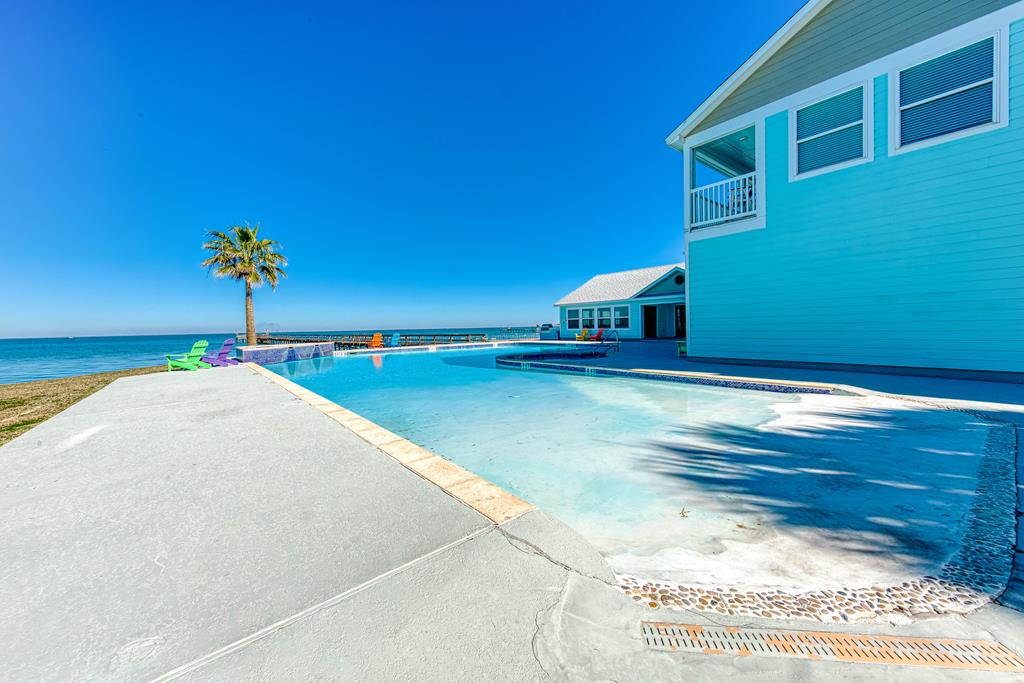 Incredible Copano Bayfront Gated Community. The condo has a 35' Boat Garage- a must have for any fisherman- plenty of room for storage, tackle & toys! The lower level bedroom is great for an overflow of guests. Head upstairs and fall in love with your bay views from the expansive living room w/ raised ceiling & plenty of space to host a small crowd. Each bedroom has it's own full bathroom. Being sold furnished except for personal items, this retreat is as turn key as they come. A third level bedroom and powder room is fantastic for even more company to have their own space. Private and secure, Gables of Copano Vista is an impeccably maintained community in a prime location. Gables of Copano Vista boasts a zero entry pool that overlooks the gorgeous Copano Bay, a bay brimming with Redfish and record breaking trout! The 400' pier is perfect for evening fishing with loved ones and if you're wanting to hold a big fish fry for guests and neighbors, check out the amazing Club house!