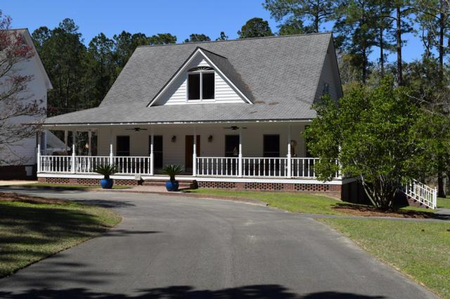 Gated and fenced 18.66 +/-acres, 2170 +/- sq. ft., 3 BR/ 2 ? BA home built in 2004.  Hardwood flooring, with new tile in upstairs bath.Kitchen features granite counter tops, custom built cabinets including TV and wet bar w/ ice maker.  Master suite on lower level has built in dresser w/TV. The 2nd level has 2 additional BR w/hardwood flooring, a foyer and bath.  Step outside in any direction and the amenities abound!  A wrap around porch gives you a view of the pond on one side w/the beauty of the pines on the other!  Step out back to a 25 x 50 salt water pool w/fountains and an entertainment area w/ storage.  Property also has an enclosed 46 x 46 storage barn with RV hook up, enough room to store a boat, car and RV! Separate bldg houses a historical, surround sound movie theater w/ original seating and ticket booth from the Rose Theater. The theater includes a kitchenette and full bath upstairs w/additional bath, storage area and 1 car garage on lower level. A one-of-a kind place!