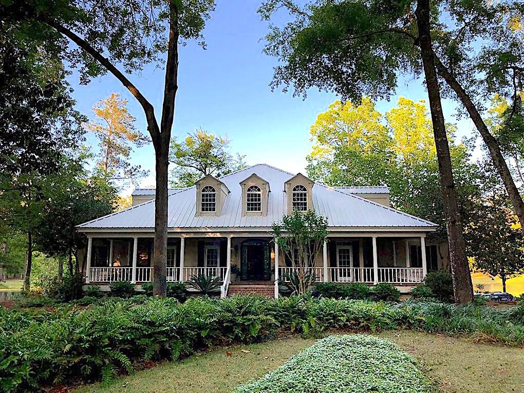 Beautiful & private, this 10 ac. estate offers generous living space & sweeping lake views. The spacious low country style is true southern living at its finest. A wide, rocking chair front porch offers a gracious welcome. Be sure to take notice of the reclaimed wood floors salvaged from a local schoolhouse. Traditional dining & living rooms grace the front of the home, with comfortable family living spaces along the back. The well-appointed gourmet kitchen is a chef's dream w/ a Wolf induction cooktop, twin Thermador ovens, paneled sub zero, ice maker & more. Retreat to the main level master suite & admire the beauty of the outdoors from the soaking tub or private reading porch. Three oversized bedrooms & 2 baths are located upstairs while the lower level provides ideal bonus space with 2 BR/2 BA, great room w/ FP & full kitchen. Multiple living & entertaining spaces on the main & lower levels flow outside to pristine, natural surroundings. Just perfection!