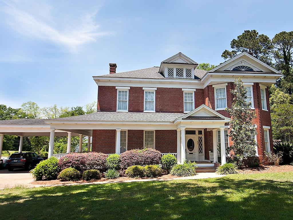 Magnificently restored historic home just steps from downtown Thomasville! An entertainer's dream, the entire home has been carefully restored with modern touches that only add to the historic charm found in every room. A beautiful wrap around porch welcomes you into a grand foyer. From there enter through original pocket doors to the front study, formal living room or formal dining room with a gorgeous custom built in china cabinet. A gourmet chef's kitchen offers two sub zeros, 8 burner Viking stove, and abundant counter area whether  preparing small family dinners or hosting large parties. Take the stairs up to the second floor hall where 4 generous bedrooms and 3 baths converge off the central hall. The large master suite with balcony offers space to relax and unwind. Travel another staircase to a huge 3rd level bonus area with built ins and unique metal ceiling that overlooks the front yard through charming windows. Almost every room in the main house has an original coal burning