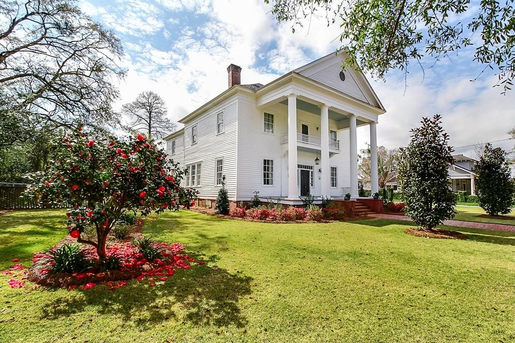 """This beautiful historic home offers over 3500 sq ft of space. It features a grand entrance with 14 ft ceilings, original 164 year old 6"""" heart pine flooring, professional landscaping with front irrigation, and a 1 acre lot that is completely fenced in in the back with lattice brick on 2 sides. Inside you will find a 14x25 master with en-suite and 3 additional 14x17 bedrooms. The rear bedroom can easily be configured into a second master with en-suite that includes a deep jetted tub, by simply closing one door. There is a separate hot water heater for each floor, as well as 2 4.5 ton AC units one with a gas furnace serving the main level. All ductwork and plumbing was replaced in 2013. Outside you will find a 410 sq ft screened in porch with a chair lift for the back staircase leading to the upper level of the home, a security system with cameras, a completely wired 20x20 workshop that was restored in 2015, and a 2 car garage. Listed in National Historic Register of Homes in 1969."""
