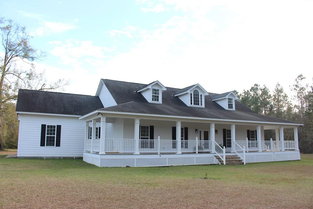 Looking for quiet living in the country?  This spacious farmhouse has it all.  Built in 2008 and nestled on nearly 5 acres, this property is sure to please!  Enjoy beautiful wooded views and tranquil evenings on the wrap around front porch, back covered porch, and deck. Home has 4 bedrooms, 2.5 baths, a bonus room (for man cave, kids playroom, etc), huge walk-in attic with endless storage space, large laundry room with sink, two AC units, and a brand new well.  Open floor plan is perfect for entertaining family and friends.  Make an appointment to see this beautiful property today!